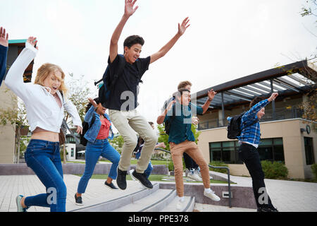 Gruppe von Schülern das Springen in die Luft außerhalb der Hochschule Gebäude - Stockfoto
