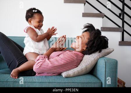 Mutter liegend auf dem Sofa zu Hause spielt, Klatschen, Spiel mit Tochter - Stockfoto