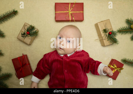 Baby Gefühl glücklich durch Weihnachtsgeschenke umgeben - Stockfoto