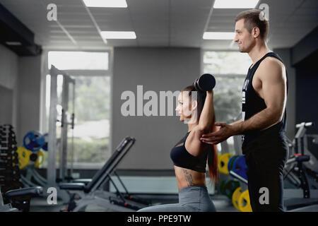Seitenansicht des stattlichen männlichen Personal Trainer helfen, muskulöse Frau Arbeiten mit schweren Hanteln im Fitnessstudio. Junger Mann motivierend schöne Client ordnungsgemäß zu Übungen ihren Körper in Ton zu halten. - Stockfoto
