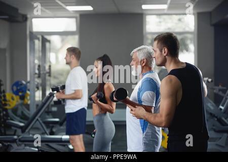 Ältere Menschen tun, Übung mit hantel im Fitnessstudio mit einer Gruppe von verschiedenen jüngeren Menschen, die Workout mit gleicher Ausstattung. Team zusammen arbeiten unter Aufsicht von persönlichen Coach, Ausbildung ihrer Muskeln. - Stockfoto