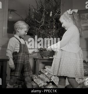 """1950 s, historischen, einen Jungen und Mädchen eine Christmas Cracker vor einem kleinen geschmückten Weihnachtsbaum und eine mit Haufen präsentiert unter, England, UK. Die traditionelle Herausziehen von Crackern ist dazu gedacht, die auf der Mitte der 1850er Jahre bis jetzt, wenn Sie zum ersten Mal von einem Mann namens Tom Smith, der seine Idee von der """"Knistern"""" ein offenes Feuer gemacht wurden. - Stockfoto"""