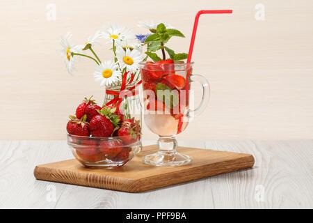 Kohlensäurehaltige Limonade mit Erdbeere und Minze auf einer hölzernen Schneidebrett, kalte Getränke für heiße Sommer Tag - Stockfoto
