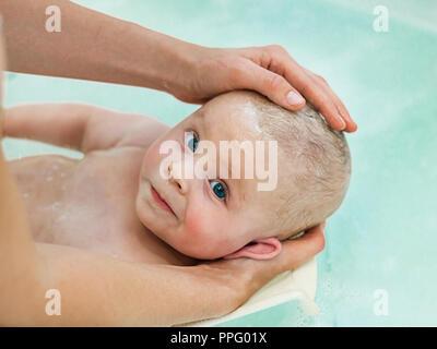 6 Monat Baby in der Badewanne. Kleines Kind in einer Badewanne. Kleinkinder Waschen und Baden. Nicht erkennbare Mutter ihr Baby baden. - Stockfoto