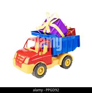 Mehrfarbige Kunststoff Spielzeug-LKW trägt Geschenkboxen mit dekorativen Bändern im Körper gebunden, auf weißem Hintergrund - Stockfoto
