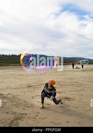 Eine junge Frau versucht, eine große Seifenblase in der Luft bei einer eine Blase blasen Festival am Strand in der Nähe von Yachats, Oregon zu halten. - Stockfoto