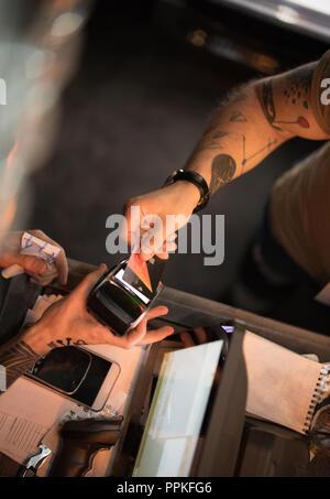 Der Mann zahlt mit eine Kreditkarte mit einem Barkeeper in einer Bar - Stockfoto