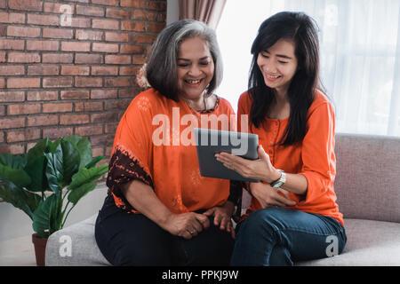 Ältere Mutter und ihre erwachsene Tochter mit Tablet - Stockfoto