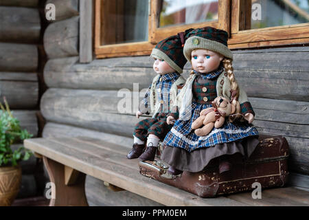 Antike porzellan Puppen sitzt auf Koffer in der Nähe von Bauernhaus anmelden. - Stockfoto