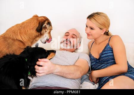 Stattlichen Paare mit ihren Hunden auf dem Bett am Morgen. Junger Mann und Frau verbringt Zeit mit ihren Haustieren im Schlafzimmer. Glück Paar genießen. - Stockfoto