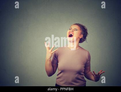 Junge chunky Frau laut schreiend in der großen Hysterie auf grauem Hintergrund - Stockfoto