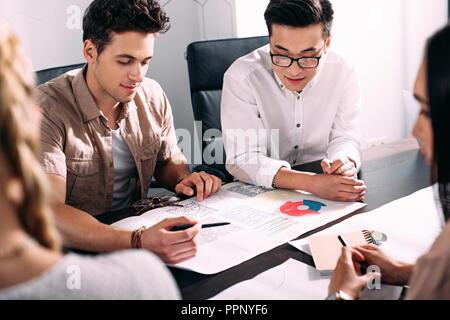 Zwei multiethnischen Geschäftsleute in Sitzung am Tisch mit Grafiken in modernen Büro - Stockfoto