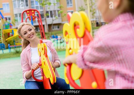 Zugeschnittenes Bild von Mädchen reiten auf Schaukelpferd mit lächelnden Mutter am Spielplatz - Stockfoto