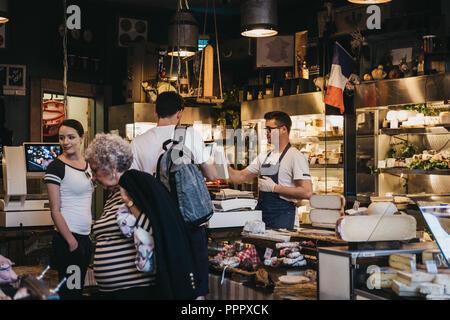 London, UK - 17. September 2018: Verkäufer und Kunden in Wurstwaren und Käse stehen in Borough Markt, eines der größten und ältesten Lebensmittelmarkt - Stockfoto