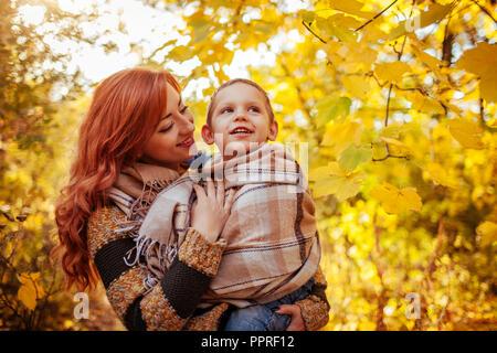 Glückliche Mutter und ihren kleinen Sohn gehen und Spaß haben im Herbst Wald. Frau wickelt ihr Kind in einem Schal - Stockfoto