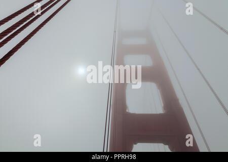 Morgen Sonne scheint durch den dicken Nebel an der Golden Gate Bridge auf einer späten Sommer Tag, San Francisco, Kalifornien, USA - Stockfoto