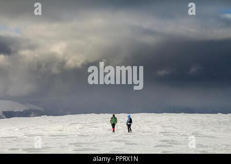 Winter Berglandschaft. Rückansicht des reisenden Touristen Wanderer mit Rucksack auf schneebedeckten Feld und laufen Sie in Richtung des entfernten Berg auf bewölkt dunkel blau St - Stockfoto