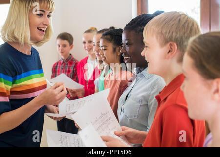 Kinder im Schulchor gefördert durch Lehrer - Stockfoto