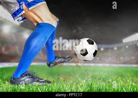 Fußball-Spieler in Aktion mit Fußball in Hell outdoor Stadion beleuchtet. Fokus auf Vorder- und Fußball mit einer geringen Tiefenschärfe auf dem Hintergrund einer - Stockfoto