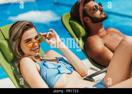 Junges Paar in Sonnenbrille entspannen auf Sonnenliegen am Pool - Stockfoto