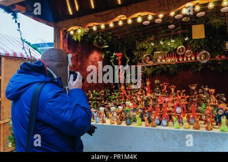 Mann Fotografieren der Abschaltdruck am Weihnachtsmarkt am Kaiser-Wilhelm-Gedächtniskirche im Winter Berlin, Deutschland. Christkindlmarkt Dekoration und Ständen mit - Stockfoto