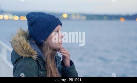 Frau in Gedanken verloren lehnt sich an der Reeling eines Kreuzfahrt Schiff - Stockfoto