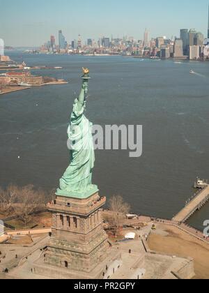 Die Freiheitsstatue mit Manhattan im Hintergrund von einem Helikopterflug über New York Bay gesehen - Stockfoto