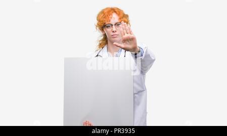 Junge rothaarige Arzt Frau mit Banner mit offener Hand das STOP-Schild mit ernsten und selbstbewussten Ausdruck, Verteidigung Geste - Stockfoto