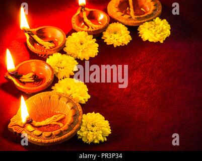Traditionelle Ton diya Leuchten mit Blumen für Diwali Festival feiern. - Stockfoto