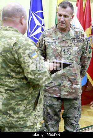 Ukrainische Col. Gen. 363 Popko (links), Kommandeur der ukrainischen Land Forces Command, präsentiert ein Geschenk der US-amerikanischen Armee Generalleutnant John Thomson (rechts), Kommandeur der NATO-Verbündeten Land Befehl (LANDCOM), nach der Unterzeichnung der Zusammenarbeit zwischen der Ukraine und der NATO Kommando Landstreitkräfte Allied Land Befehl bei schnellen Trident, Sept. 6 an der internationalen Friedenssicherung Security Center in der Nähe von Yavoriv, Ukraine. - Stockfoto
