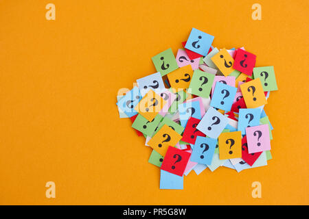 Zu viele Fragen. Stapel der bunten Papier nimmt mit Fragezeichen auf gelben Hintergrund. Nahaufnahme. - Stockfoto