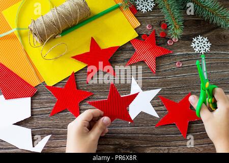 Das Kind schneidet den details Weihnachtsbaum Spielzeug star Geschenk. Handgefertigt. Projekt der Kreativität der Kinder, Kunsthandwerk, Handwerk für Kinder. - Stockfoto