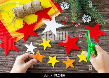 Das Kind schneidet den details Weihnachtsbaum Spielzeug Geschenk. Handgefertigt. Projekt der Kreativität der Kinder, Kunsthandwerk, Handwerk für Kinder. - Stockfoto