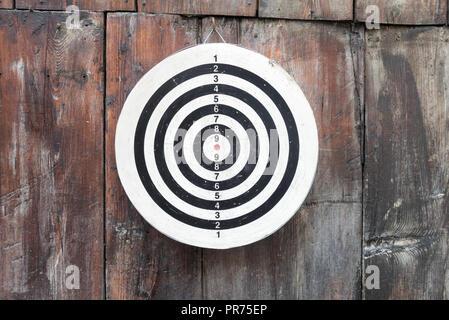 Runde Runde schwarz und weiß Target mit Zahlen hängen an eine Holzwand in der Nähe und im Detail - Stockfoto