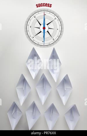 Abstrakte Kompass mit Nadel nach das Wort Erfolg auf der Vorderseite des Papiers Boot. Konzept Team erfolgreich oder ein Geschäftskonzept. - Stockfoto