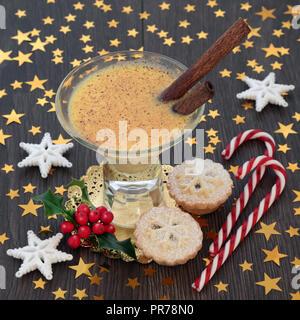 Weihnachten Eierlikör traditionelles Getränk mit Mince Pies, Zuckerstangen, star Dekorationen und Winter Stechpalme auf Eiche rustikal Tisch Hintergrund. Festliche Thema. - Stockfoto