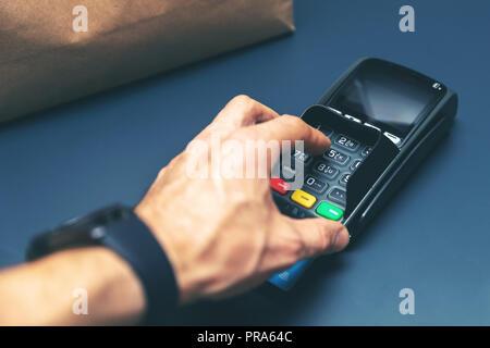 Kreditkarte kaufen bei Store hand Eingabe PIN-Code - Stockfoto