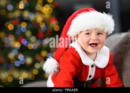 Baby lachen Tragen santa claus auf der Couch zu Hause in Weihnachten mit einem Baum im Hintergrund der Verkleidung - Stockfoto