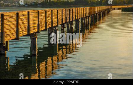 Den Sonnenuntergang malt die historische Fußgängerzone holzsteg Brücke über den oberen Zürichsee (Obersee) in einem Honig Gold Farbe. Ein Teil der alten des Sai - Stockfoto