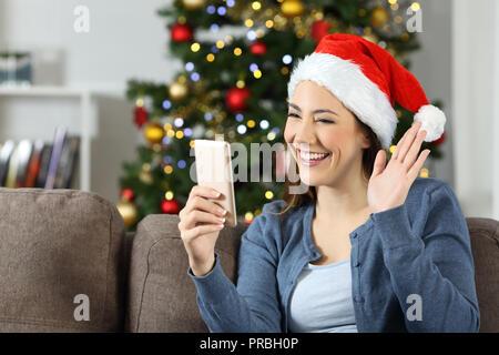 Die Frau winkt bei einem Smart Phone video Anruf in Weihnachten auf einer Couch im Wohnzimmer zu Hause sitzen - Stockfoto