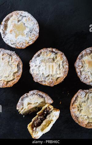 Mince Pies, traditionelle Weihnachten Lebensmittel aus allen Butter mürbteig Gebäck Torten tiefe gefüllt mit pralle Reben Früchte, wie Preiselbeeren, Clementine - Stockfoto