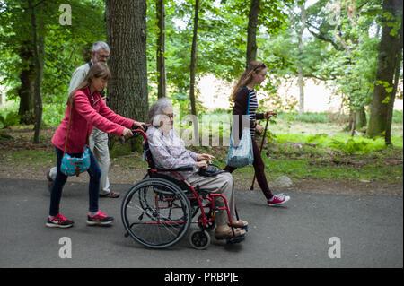 Alte Frau im Rollstuhl von ihrer Enkelin mit anderen Mitgliedern ihrer Familie an crathes Castle Aberdeenshire Scotland gedrückt wird - Stockfoto