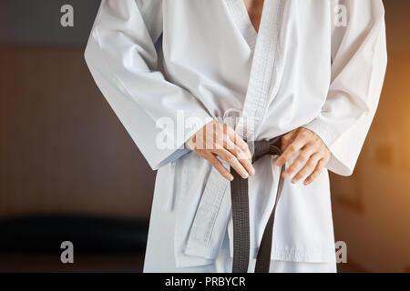Hände anziehen Black Belt auf Mann in Kimono gekleidet - Stockfoto
