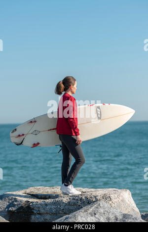 Frau steht auf Felsen mit einem Surfbrett im Meer vor dem Surfen. - Stockfoto