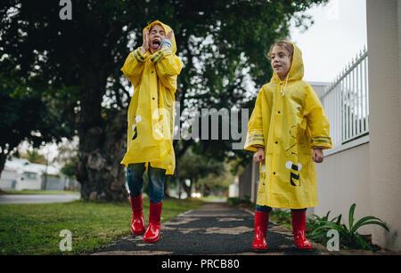 Zwei kleine Kinder im Freien auf regnerischen Tag. Zwillingsschwestern Spaß draußen tragen wasserfeste Kleidung und regen Stiefel. - Stockfoto