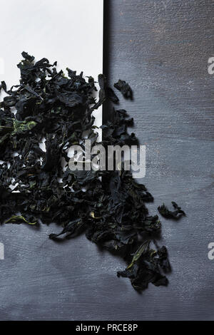 Hohe Betrachtungswinkel und einem Haufen getrockneter Blätter von Wakame, einem Asiatischen essbare Algen in der traditionellen Suppen wie die Miso Suppe verwendet werden, auf einem weißen Teller platziert - Stockfoto
