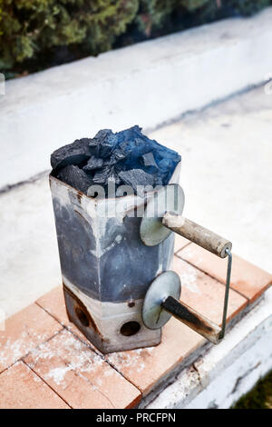 Rauchen Holzkohle Chimney Starter Schaufel für Grill in einem Garten im Hinterhof - Stockfoto