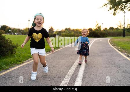 Zwei kleine Schwestern laufen auf der Straße in den Park an einem sonnigen Sommertag. Süße kleine Mädchen. - Stockfoto