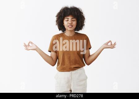 Innen- schuss der Ruhe und des stilvollen pacient urban Studentin mit Afro Frisur und dunkle Haut schließen Augen lächeln sorglose Verbreitung Hände beiseite in zen Geste meditieren und Linderung von Stress - Stockfoto