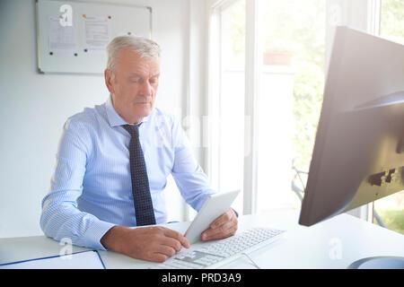 Aufnahme eines Senior Bank Officer mit digitalen Tablet beim Sitzen im Büro und arbeiten auf der Anlagestrategie. - Stockfoto